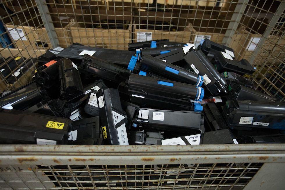 viele gebrauchte Tonerkartuschen in einer Metallschütte