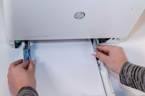 Druckerpapier wird in Papierfach mit Schieberegler fixiert