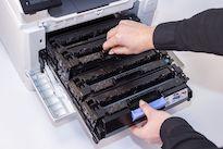 Tonerkartusche wird aus geöffnetem Laserdrucker entnommen