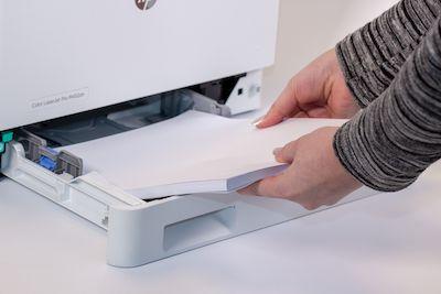 in eine Drucker-Papierkassette wird Papier eingelegt
