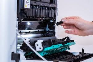 Das Innere eines Druckers wird mit Taschenlampe nach Fremdkörpern abgesucht